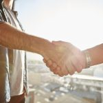 Closeup of two shaking male hands with sun flare. Focus on handshake against cityscape.